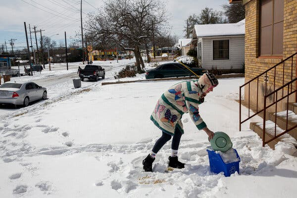 Rebecca Wright fills a recycling bin full of snow to boil into drinking water outside her home in Austin, Tuesday. Wright has been without water for nearly 24 hours when a pipe burst.