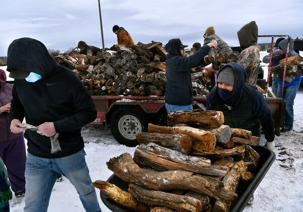 Trucks of firewood await pickup in Abilene, Texas, as people struggle to keep warm this week without power.