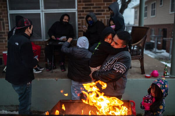 With no electricity, Eric Traugott and his son warmed up by a fire outside their apartment in Austin, Texas, on Wednesday.