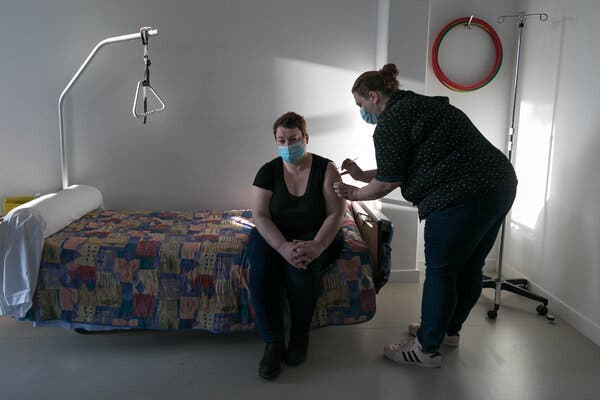 A nursing home employee got a coronavirus vaccination in Versailles, France, this month. France trails neighbors like Germany and Italy in the proportion of people vaccinated.