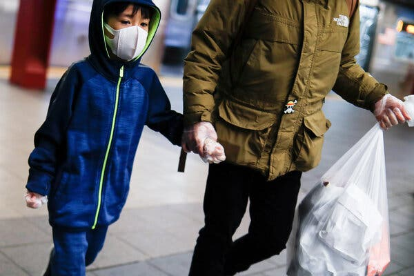 A child wore a protective mask and gloves in a New York subway station early in the pandemic.