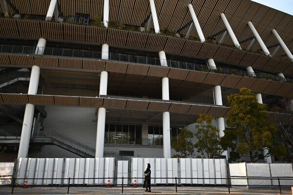 A woman walks outside the National Stadium, the main venue for the opening and closing ceremonies for the Summer Olympics Games in Tokyo on February 11, 2021.
