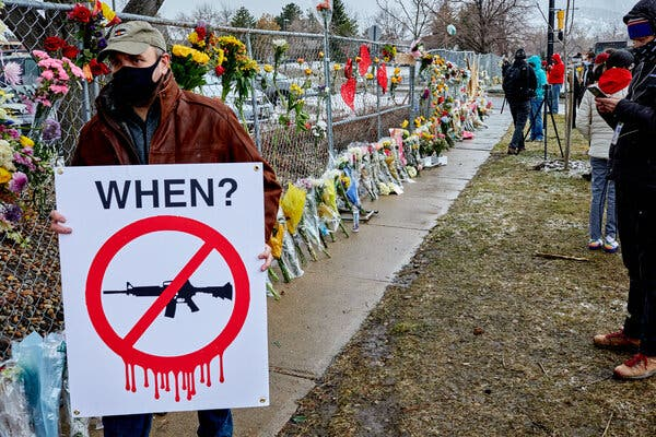 A man bearing an anti-gun sign walks past the memorial for those killed in the mass shooting at the Mesa Drive King Soopers in Boulder, Colo.