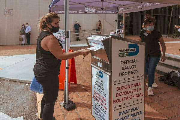 A poll worker depositing a mail-in ballot at a drop box in Westchester, Fla., in October. New legislation in Florida reduces the amount of drop boxes used for voting.