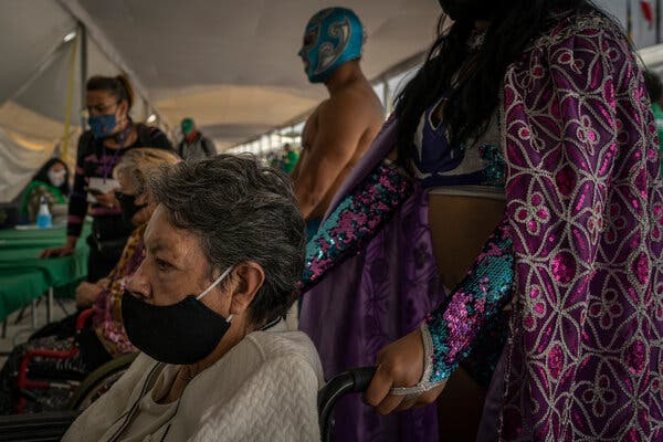 Lucha Libre wrestlers wheeling patients inside a vaccination tent in Mexico City this month.