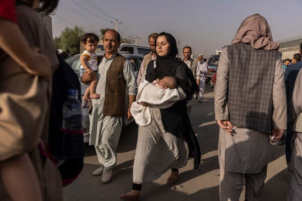 Afghans trying to enter the military side of the Hamid Karzai International Airport in Kabul on Thursday.