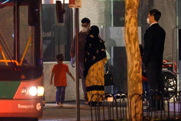 A family, among more than 90 evacuated Australian citizens and Afghans, stepping off a bus at a hotel to begin a pandemic quarantine in Perth on Friday.