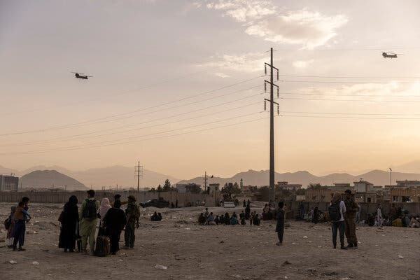 Helicopters flying over a crowd of Afghans gathered outside the airport in Kabul on Monday.
